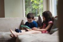Siblings using digital tablet in living room at home — Stock Photo