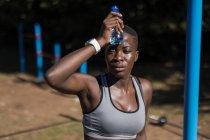 Close-up de atleta feminina exausta com garrafa de água — Fotografia de Stock