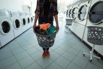 Partie médiane de la femme tenant un panier à linge à la laverie automatique — Photo de stock