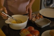 Mid section of woman preparing breakfast in kitchen at home — Stock Photo