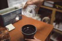 Женщины фотограф заливки химического вещества на крышку объектива в фото студии — стоковое фото