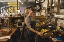 Junge Frau stellt Gemüsetablett auf den Küchentisch im Café — Stockfoto