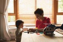 Мати, грати з сином на столі вдома — стокове фото