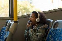 Девочка-подросток ест кексы во время прослушивания музыки в наушниках в автобусе — стоковое фото