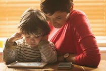 Close-up of mother and son sitting with a digital tablet at home — Stock Photo