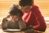 Primo piano della madre e figlio che si siedono con una tavoletta digitale a casa — Foto stock