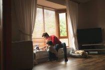 Madre che gioca con il figlio sul davanzale della finestra in soggiorno a casa — Foto stock