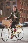 Bella donna che utilizza il telefono cellulare mentre si guida in bicicletta sulla strada — Foto stock