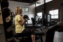 Femme handicapée exerçant sur ordinateur dans la salle de gym — Photo de stock
