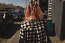 Vista posteriore di una giovane donna che cammina attraverso un marciapiede — Foto stock