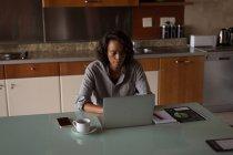 Mujer usando portátil en mesa de comedor en casa - foto de stock