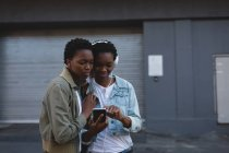 Twins siblings listening music on mobile phone in city street — Stock Photo