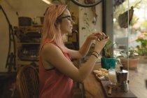 Молодая женщина фотографирует еду, подаваемую на стол в кофейне — стоковое фото