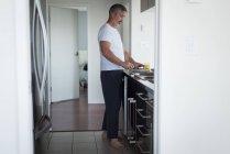Homem preparando café da manhã na cozinha em casa — Fotografia de Stock