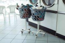 Deux paniers à linge près de la machine à laver à la laverie automatique — Photo de stock