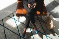 Vista de alto ângulo de empresária sentada com as pernas cruzadas usando telefone celular — Fotografia de Stock