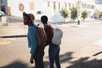 Брати і сестри близнюки стояли з рюкзак в міській вулиці — стокове фото