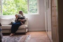 Mère jouant avec bébé sur le canapé à la maison — Photo de stock