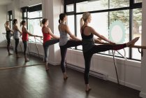 Low section of group of women practicing leg stretching on barre at the gym — Stock Photo