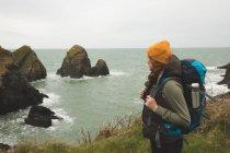 Seitenansicht einer Wanderin, die an der Küste auf das Meer blickt — Stockfoto