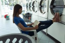 Young woman reading a book at laundromat — Stock Photo