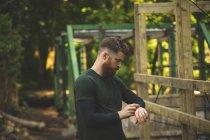 Hombre en forma usando smartwatch en el campamento de arranque en el día soleado - foto de stock