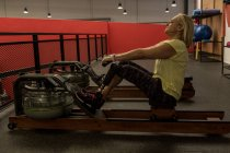 Disabled woman exercising on a machine in the gym — Stock Photo
