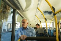 Senior man looking through window while travelling in the bus — Stock Photo