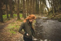 Beautiful female hiker looking at the shallow river in the forest — Stock Photo