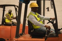 Рабочий мужчина за рулем погрузчика на складе — стоковое фото