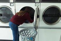 Jeune femme faisant la lessive dans la laverie automatique — Photo de stock