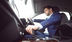 Smart businessman driving a car — Stock Photo