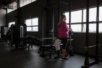 Інваліди зріла жінка за допомогою мобільного телефону в тренажерному залі — стокове фото