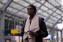 Giovane donna che prende un caffè alla stazione ferroviaria — Foto stock