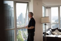 Thoughtful man looking through the window at home — Stock Photo