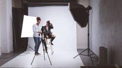 Mujer fotógrafa y modelo interactúan uno con el otro en estudio fotográfico - foto de stock
