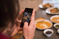 Haga clic en la foto de la comida en la cocina en la casa de la mujer - foto de stock