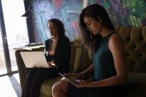 Деловая женщина с использованием ноутбука и планшета, сидя на диване в офисе — стоковое фото