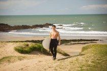 Surfista con il surf camminando sulla spiaggia in una giornata di sole — Foto stock