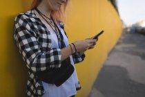 Молодая женщина, с помощью мобильного телефона на тротуар — стоковое фото