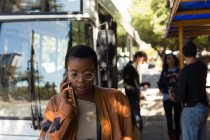 Woman talking on mobile phone at bus stop — Stock Photo