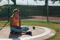 Jeune athlète féminine relaxant au lieu de rendez-vous sportifs — Photo de stock