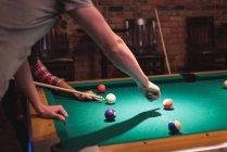 Пара, играющая в бильярд в ночном клубе — стоковое фото