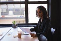 Бизнесмен читает документы во время работы на ноутбуке в офисе — стоковое фото