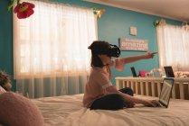 Девочка использует гарнитуру виртуальной реальности с ноутбуком в спальне дома — стоковое фото