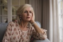Close-up of worried senior woman sitting on the sofa at home — Stock Photo