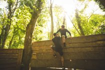 Fit man assisting his teammate to climb a wooden wall at boot camp — Stock Photo