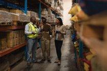 Сотрудники обсуждают через буфер обмена в складе — стоковое фото