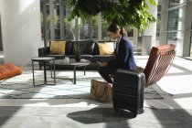 Businesswoman with suitcase using phone waiting in lobby in office — Stock Photo
