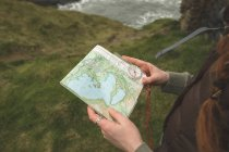 Close-up of female hiker reading a map at the sea coast — Stock Photo